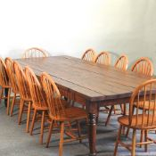 A large stained pine dining table, with a plank top, 337 x 124cm,