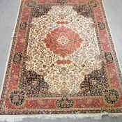 A keshan style rug, with a central medallion and foliate design, on a cream ground,