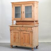 A 19th century pine dresser, with a glazed upper section,