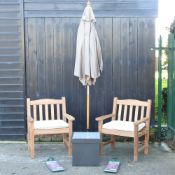 A pair of hardwood garden armchairs, with cream loose cushions, and covers,