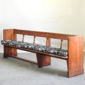 An antique pine pew, of large proportions, with a cushion seat,