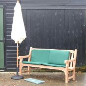 A hardwood garden bench, with green loose cushions, and cover, 183cm,