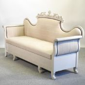 A Victorian style grey painted scroll end sofa, with an upholstered seat,