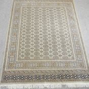 A Bokhara style carpet, with rows of medallions on a green ground,
