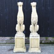 A pair of reconstituted stone models of greyhounds, each on a plinth,