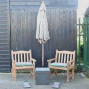 A pair of hardwood garden armchairs, with green striped loose cushions, and covers,
