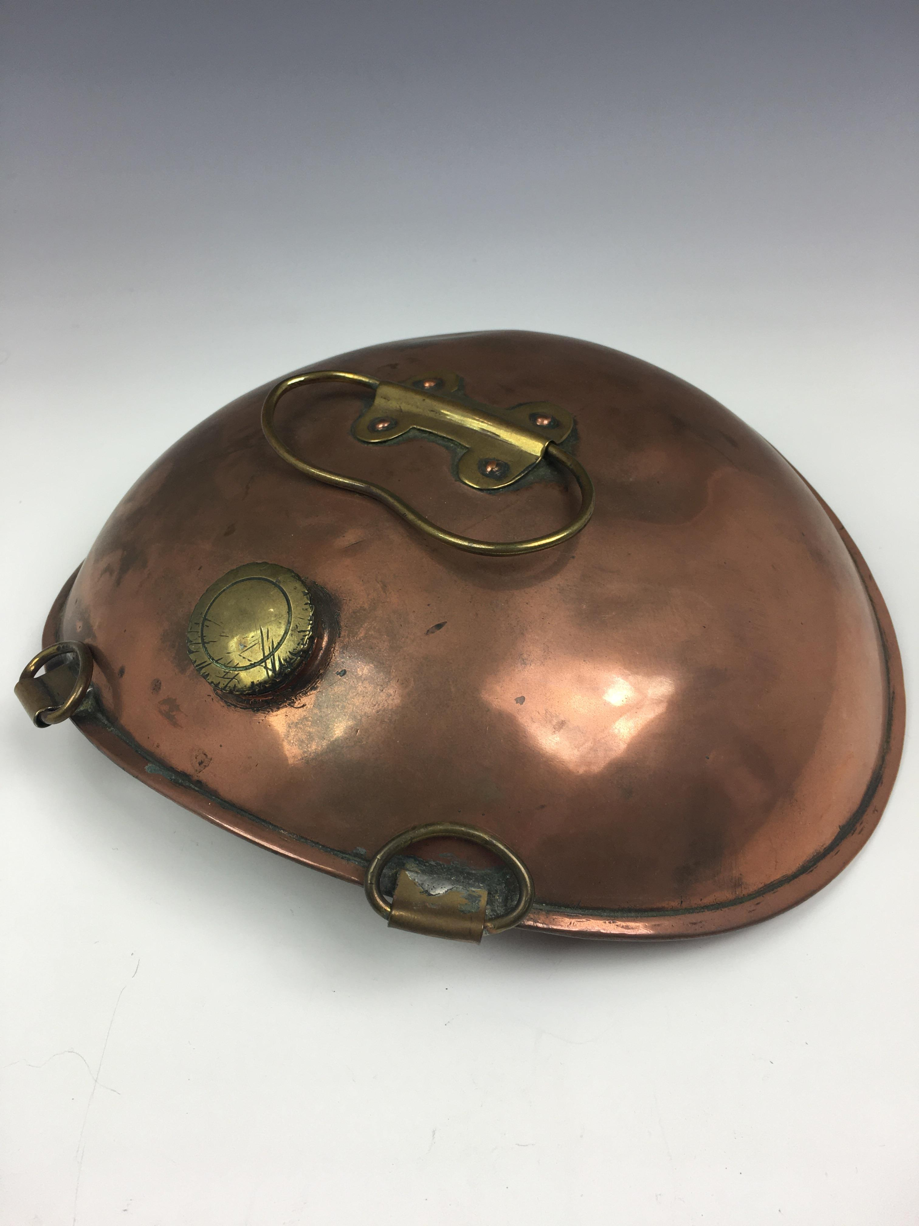 Lot 370 - An antique oval dished copper belly warmer, probably Victorian, having brass suspension strap