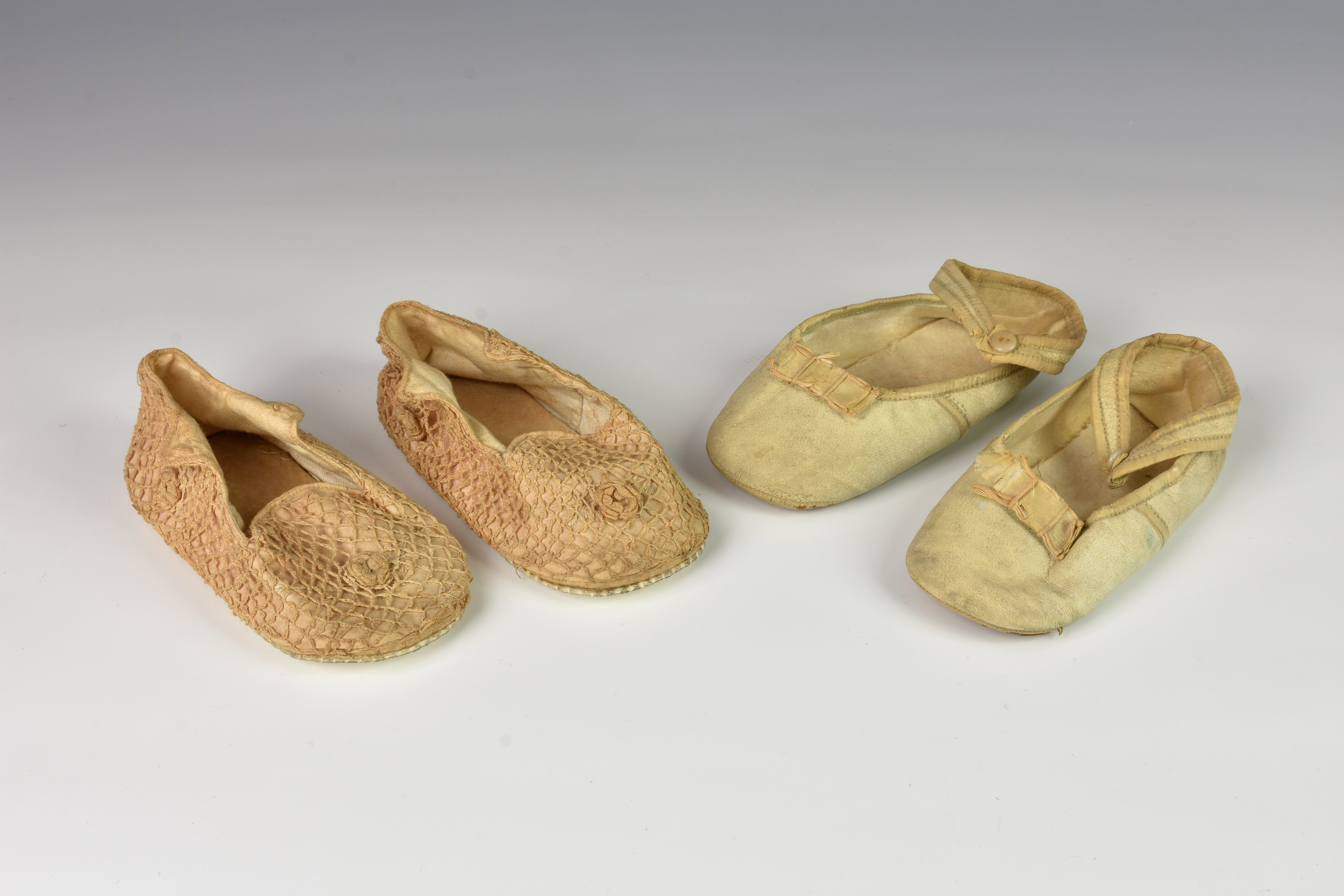 Lot 334 - Two pairs of Victorian dolls shoes, comprising of a leather pair with button down side flaps and a
