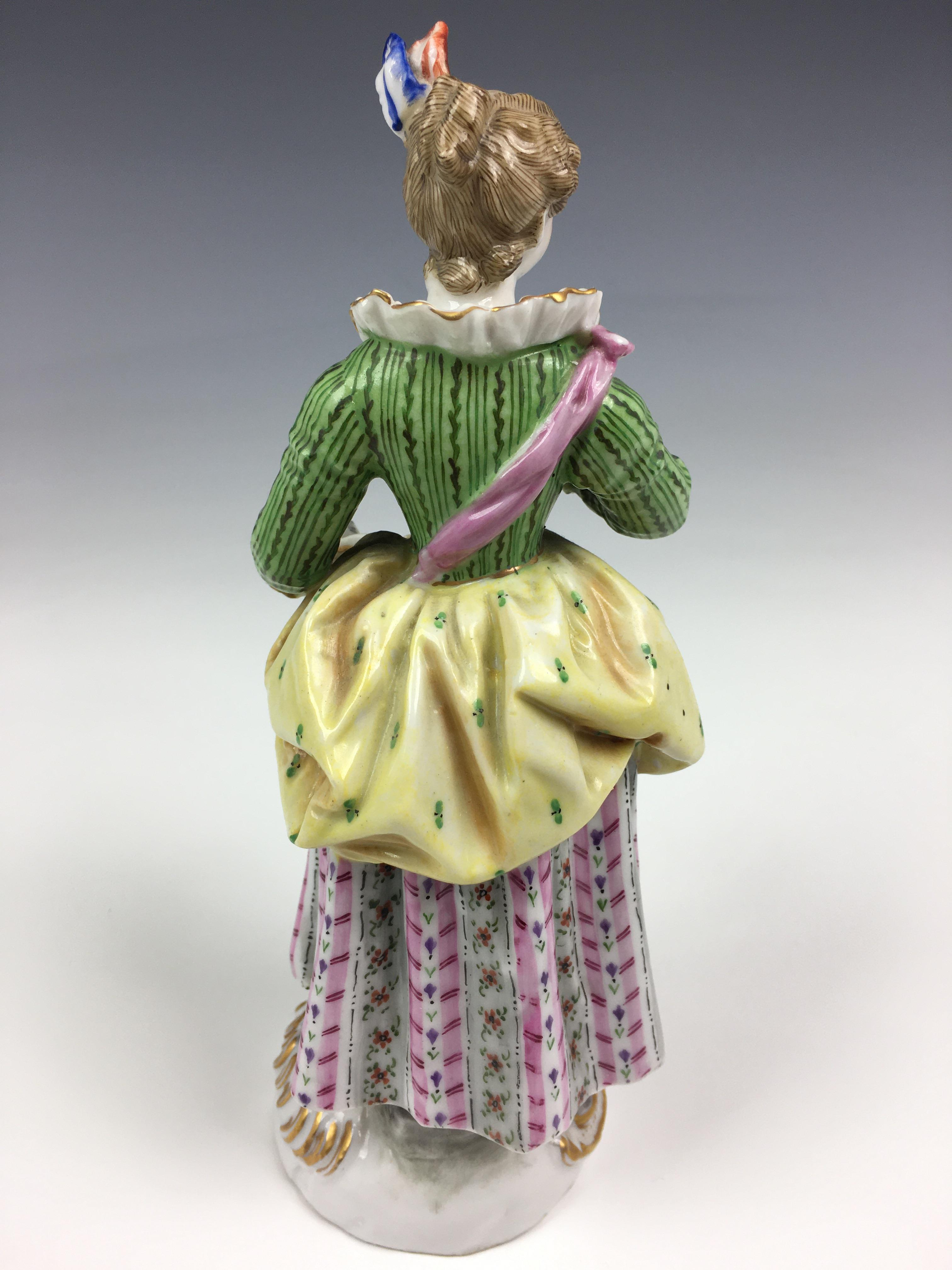 Lot 59A - A Meissen style figure of a girl holding a music book, early 20th century, Continental, in a green