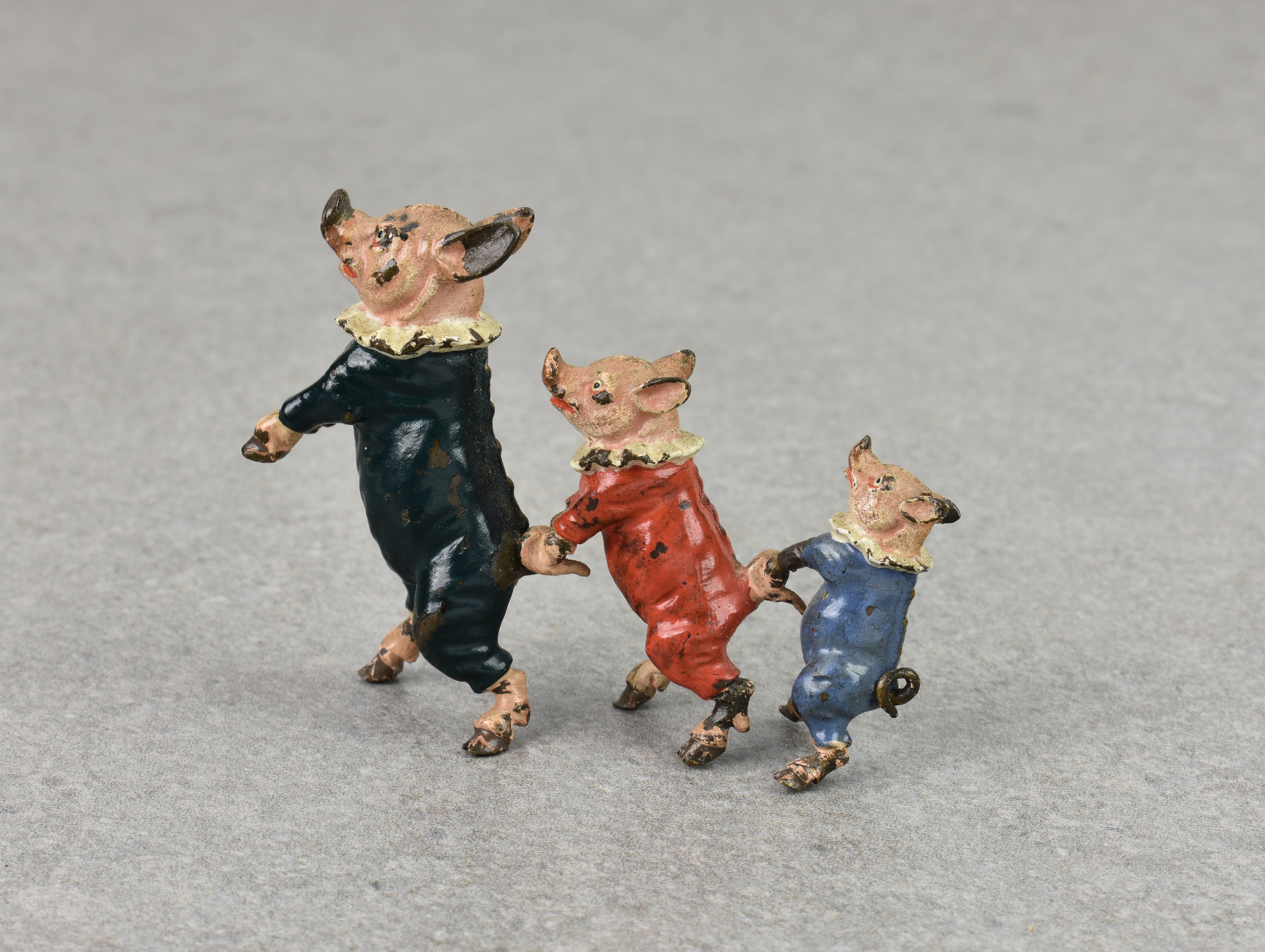 Lot 435 - A novelty miniature cold painted Vienna bronze group of three dressed little pigs in a line,