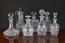 A collection of seven cut glass decanters and claret jug, the jug with silver plated mounts, the