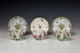 A pair of Meissen porcelain floral encrusted cabinet cups and saucers, early 'AR' mark but