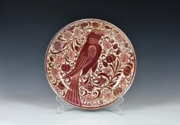 William De Morgan (1839-1917) - a ruby lustre shallow dish or charger, 1890s, painted with an