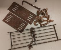 A selection of heavy cast iron: chain and hook; 2 panels with Georgian style decoration; a grate;