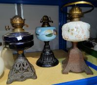 Three Victorian cast iron oil lamps with coloured glass