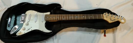 A FENDER Squire STRAT electric guitar, black body, rosewood neck with TGI soft case