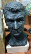 A sculpture of a male head on a sandstone base. 19' high