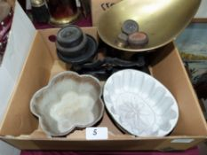 A set of weighing scales and two ceramic moulds