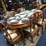 A CHINESE EXTENDING DINING TABLE WITH SIX CHAIRS