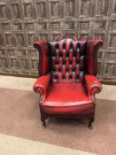 AN OXBLOOD LEATHER WINGBACK ARMCHAIR