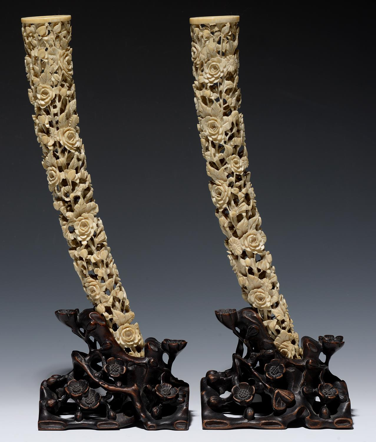 Lot 284 - A PAIR OF CHINESE PIERCED IVORY TUSK CARVINGS ON CONTEMPORARY OPENWORK HARDWOOD STANDS, CARVED AS