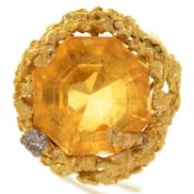 A CITRINE AND DIAMOND DRESS RING, WITH LARGER STEP CUT OCTAGONAL CITRINE, IN ABSTRACT CAST 18CT GOLD