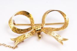 A yellow metal bow brooch with engraved finish. Pin and C catch fittings.