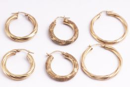 A collection of seven pairs of earrings to include hoops and drops and two odd earrings.