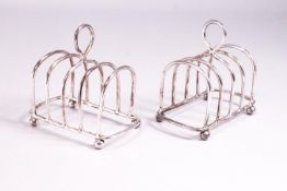 A pair of silver miniature form plain round arch toast racks with loop handles, raised on ball feet,