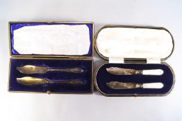 A pair of cased silver and mother of pearl butter knives, of fish knife design, Sheffield 1920,
