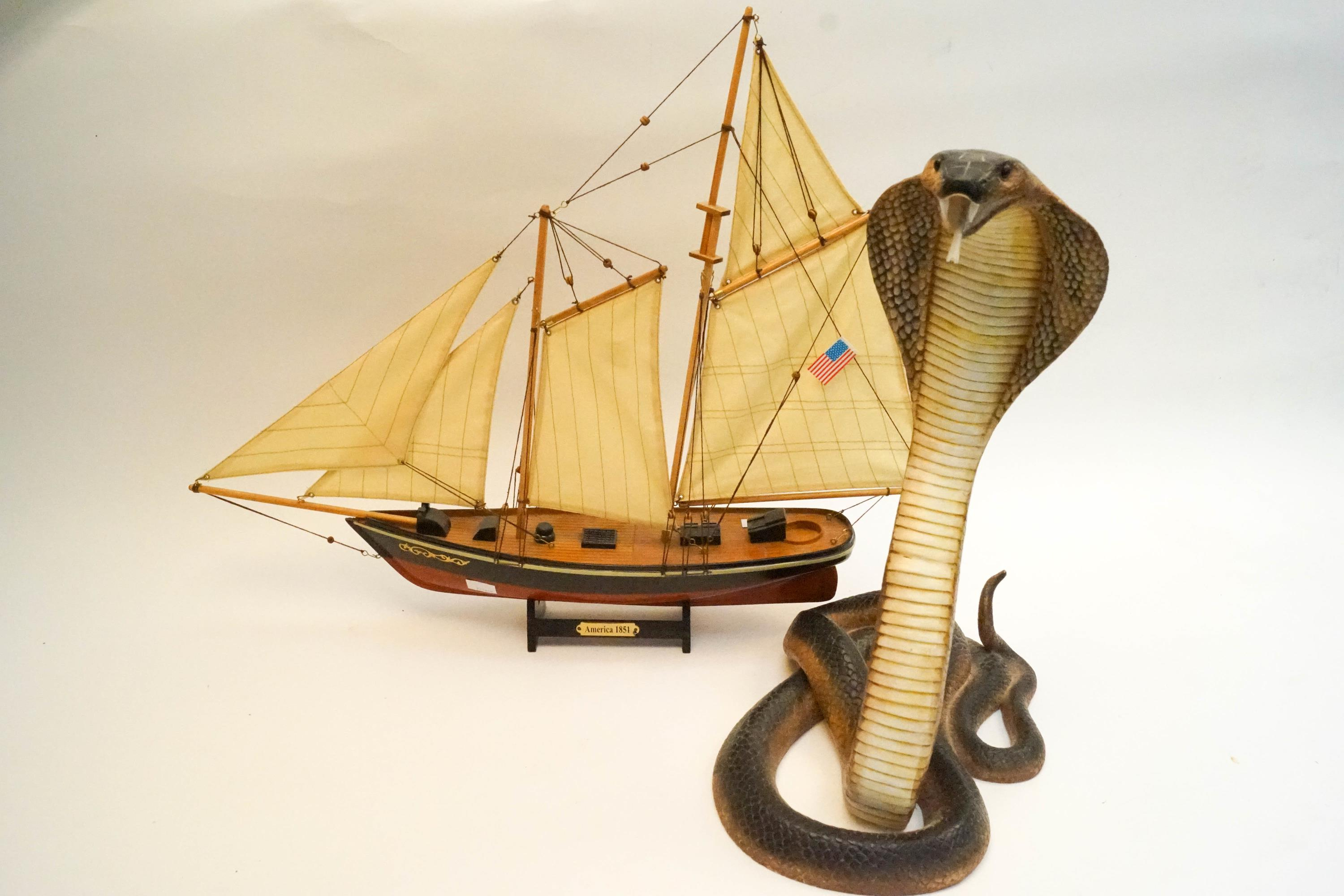 Lot 21 - A resin figure of a cobra and a model of a boat