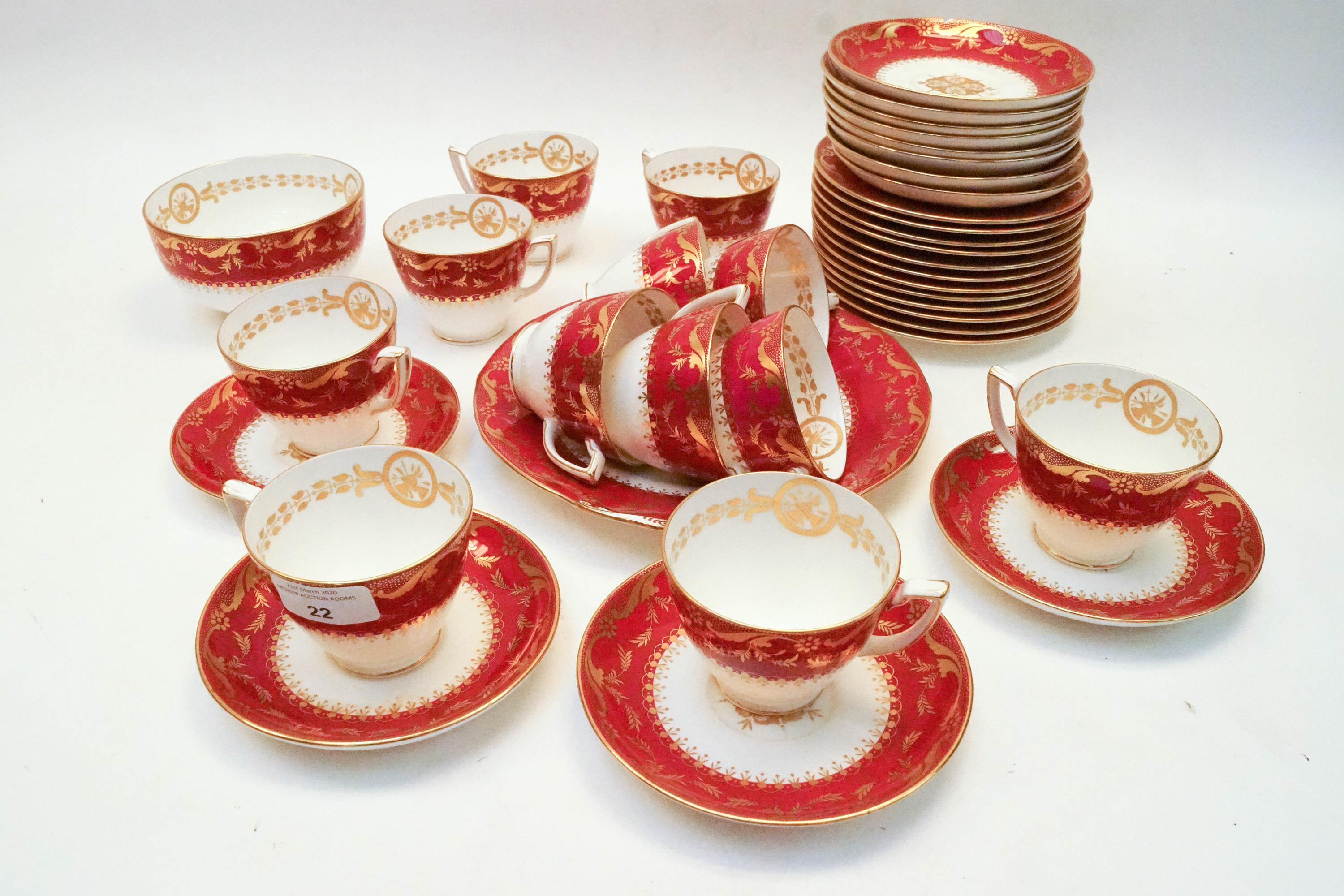 Lot 22 - A Minton dark pink ground part tea service with gilt borders of leafy tendrils,