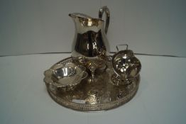 A silver eight lobed petal dish on foot, with a plated pitcher, tray and sugar bowl.