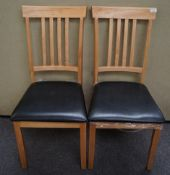 A pair of light wood dining chairs with black seats,