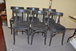 A set of six black chairs with curved back rails