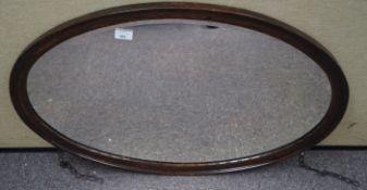 An oval oak framed mirror