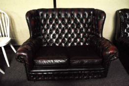 A leather button back two seat sofa