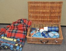 A wicker picnic hamper and two car rugs