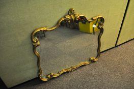 A mirror with gilt coloured frame