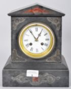 A pointed pediment slate clock with incised scrolled decoration having a white enamel face