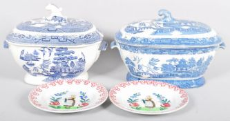 Two Quimper style plates along with two large blue and white willow pattern tureens both A/F.