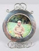 A round silver photograph frame with wire work foot and cresting, with red leather back,