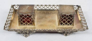 A silver desk standish, of rectangular form with angled pierced sides and raised on scroll feet,