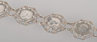 A white metal abstract linked bracelet, each set with a threepenny bit dating from 1917 to 1921.