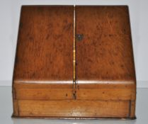 A small Victorian oak stationery cabinet with two slope front doors to a fitted interior