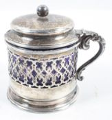 A silver mustard pot, of rounded pierced form,