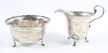 A silver helmet form cream jug, with cut card edge and scroll handle,