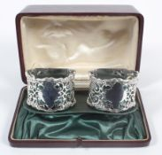 A pair of boxed silver napkin rings, of pierced geometric foliate form with cast shaped borders,