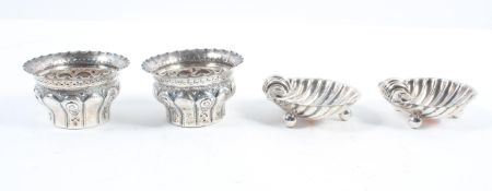 A pair of silver shell form salts, raised on ball feet,