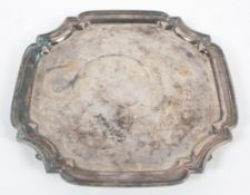A silver salver, of cut cornered square design with fancy border, raised on four scroll feet,